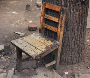 Старый стул на трех ножках у дерева